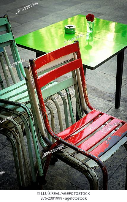 Metal color chairs stacked and a green table with an ashtray and a flower on a terrace of a bar in Plaza Real, Barcelona, Catalonia, Spain, Europe