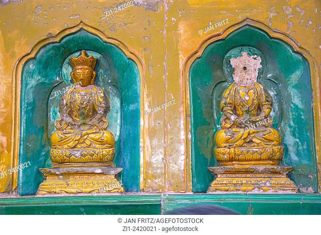 two small buddhists, one damaged, statues at temple at summer palace in beijing china