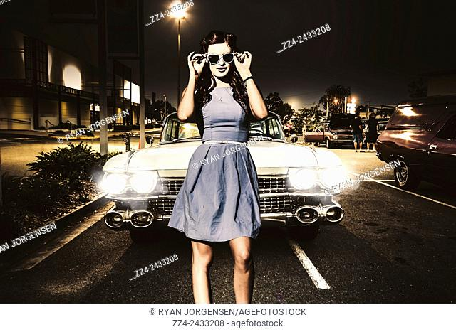 Awesome rockabilly greaser girl fashioning a signal to race in a retro carpark with her sixties Cadillac parked in two bays. 60s American car culture