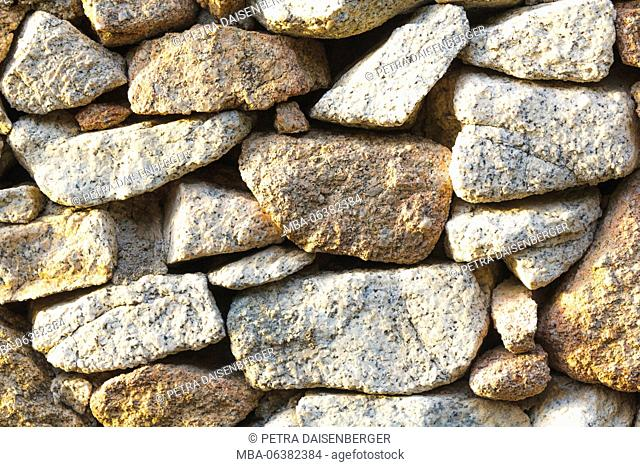 Background with conception - a stone wall in the warm sunlight
