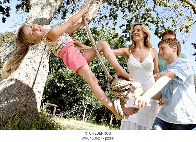 Boy pulling his sister on a rope swing with their parents beside them