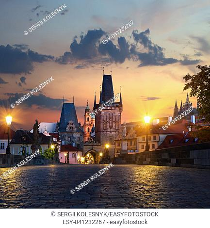 Illuminated street lights on Charles Bridge in Prague at sunrise