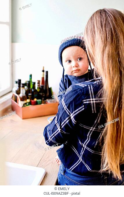 Woman carrying baby son wearing knit hat in kitchen