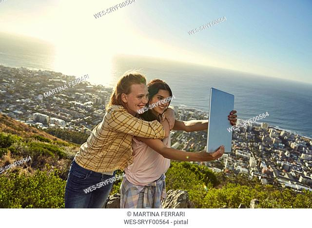 South Africa, Cape Town, Signal Hill, two young women above the city taking a selfie with tablet