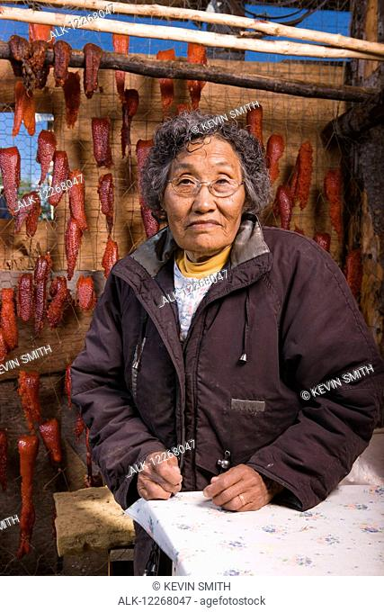 Alaska native elder woman standing in her drying shed next to filets of drying fish, Kobuk fish camp, Arctic Alaska, summer
