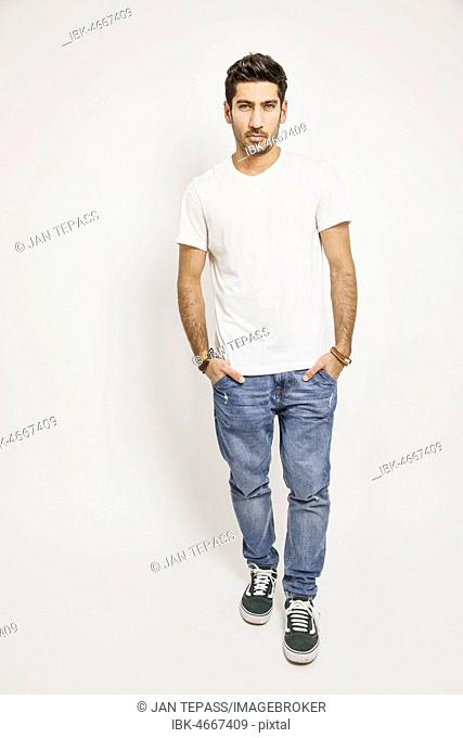 Young man, white T-shirt, jeans and sneakers, studio shot