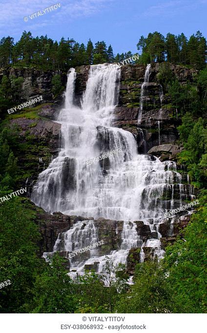 Tvindefossen Waterfall in summer sunny day, Norway