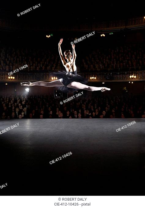 Ballerina mid-air on theater stage