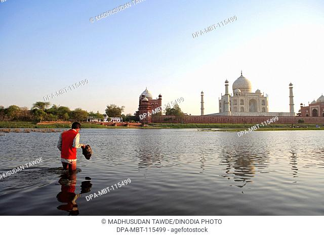 Man crossing river Yamuna at Taj Mahal Seventh Wonders of World , Agra , Uttar Pradesh , India UNESCO World Heritage Site
