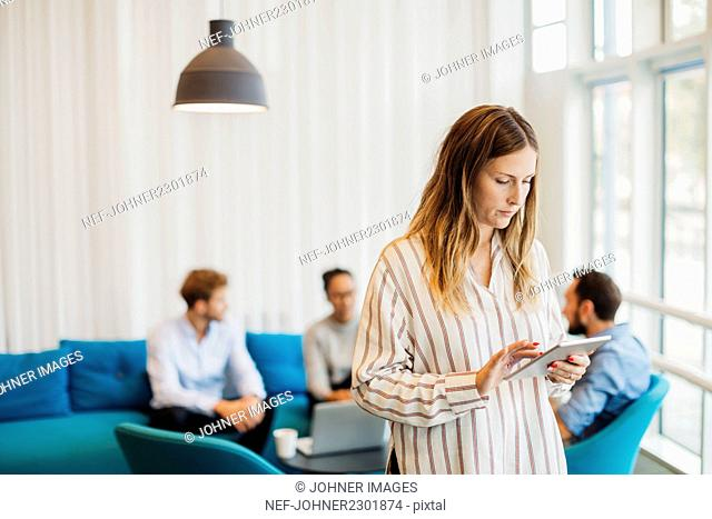 Young woman using tablet while other friends sitting in background