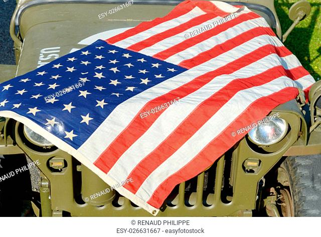 a ww2 military vehicle, jeep,with American flag