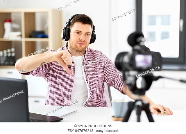 male blogger with headphones videoblogging at home
