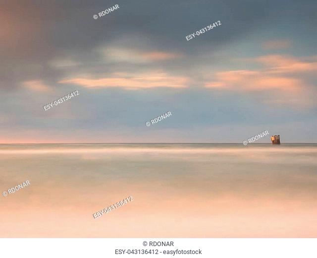 Sea birds sit on boulder sticking out from smooth wavy sea. Evening wavy ocean. Dark horizon with the last sun rays. Soft focus