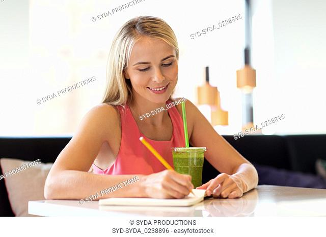 woman with drink writing to notebook at restaurant