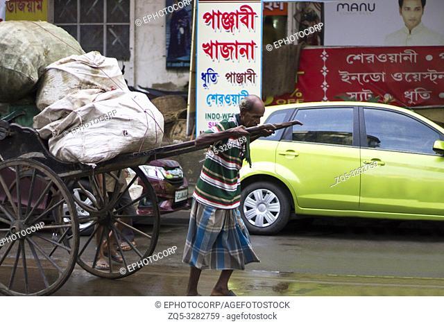 KOLKATA, INDIA, August 2017, Old man pulling hath ricksahaw or hand pulled cart on a road