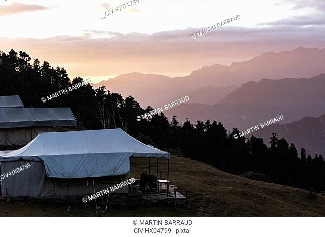 Yurts overlooking silhouetted mountains, Jaikuni, Indian Himalayan Foothills
