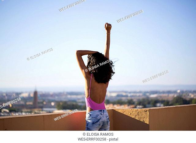 Portrait of teenage girl, raising arm, rear view