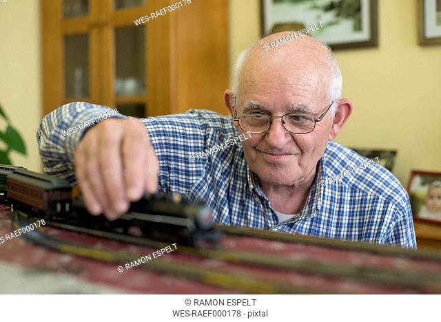 Portrait of smiling senior man with his model railway