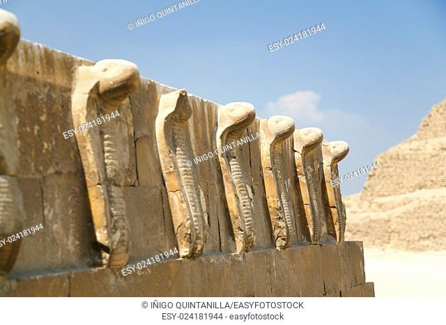 egyptian wall engraved with sculptures of cobra snakes next to Saqqara stepped Pyramid of Djoser, from year 2648 Before Christ, next to ancient Memphis city