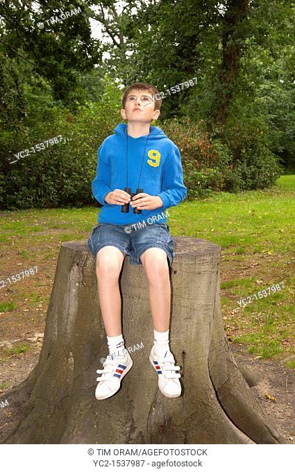 An eleven year old boy birdwatching with binoculars at Fairhaven woodland and water garden in South Walsham , Norfolk , England , Britain , Uk