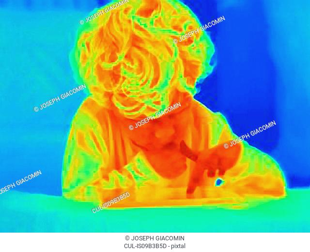 Thermal image of male toddler using digital tablet touchscreen