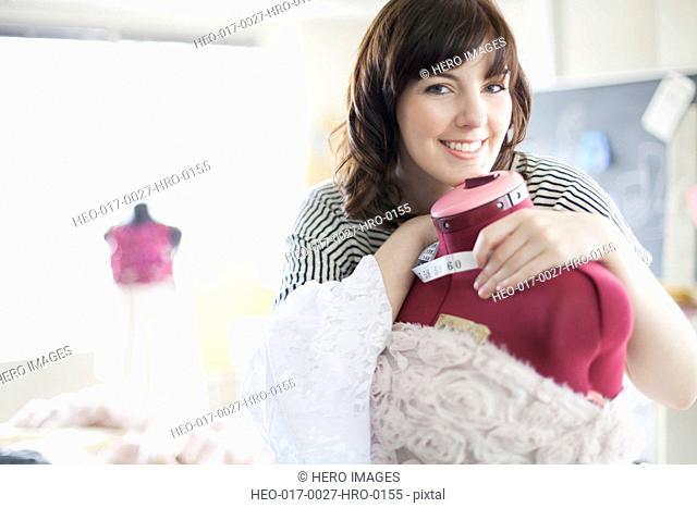 clothing designer smiling and hugging dress form