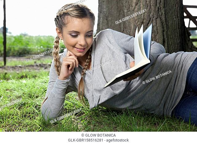 Woman reading book in a field