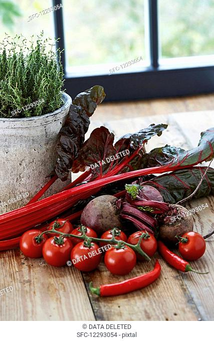 Red vegetables on a wooden table in front of a window