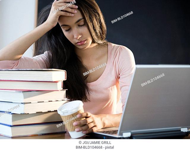 Tired Hispanic teenager holding coffee cup