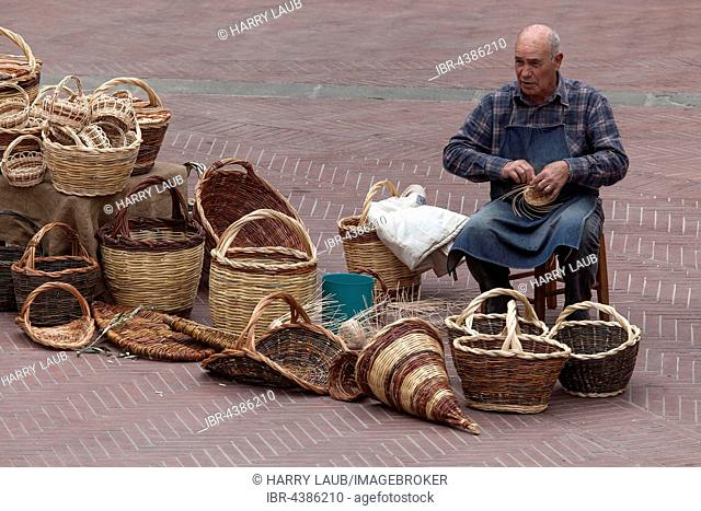 Basket weaver, man on Piazza delle Erbe making baskets, San Gimignano, Province of Siena, Tuscany, Italy