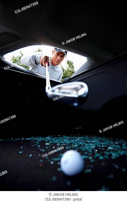 Golfer using golf club to retrieve golf ball through smashed car window
