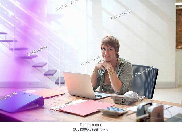 Portrait of woman at desk in creative studio