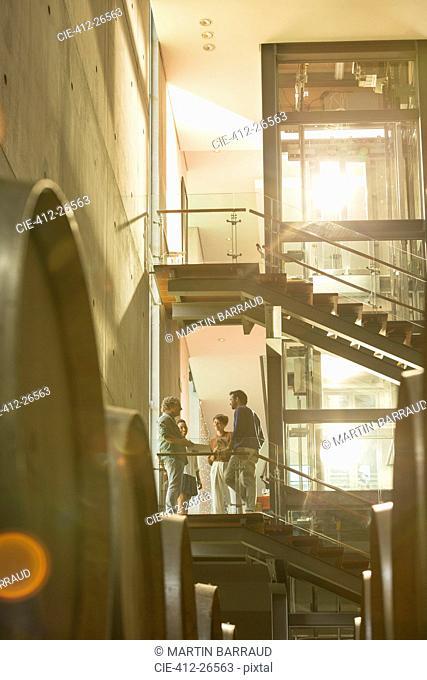 Employees talking on platform in winery