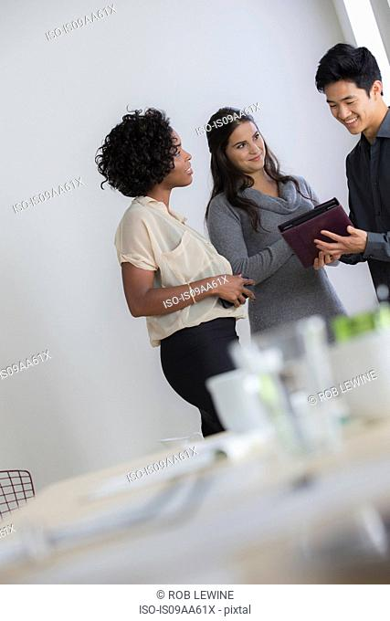 Male office worker showing file to female colleagues