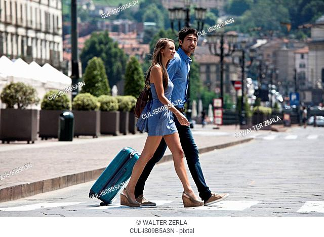 Young couple crossing road, pulling suitcase, Turin, Piedmont, Italy