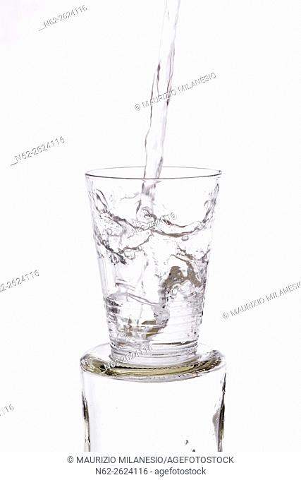 Water vigorously poured overflowing splashing from a glass, on a white background