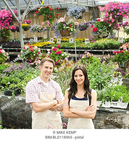 Caucasian workers smiling in plant nursery