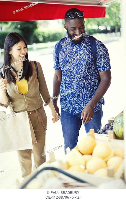 Young couple shopping for produce at market storefront
