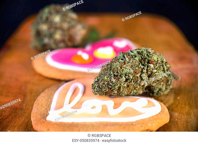 Dried cannabis nug with baked cookies on a wood tray - infused marijuana edibles concept