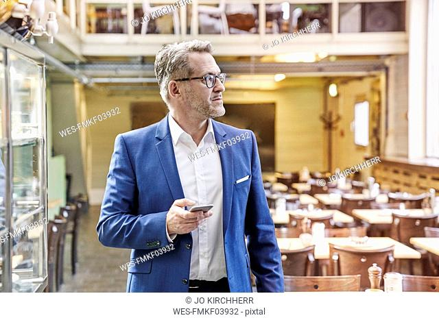 Mature businessman in cafe holding cell phone
