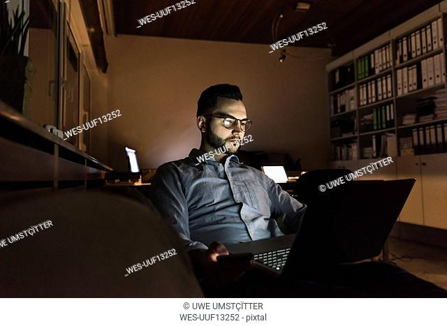 Businessman working on laptop in office at night