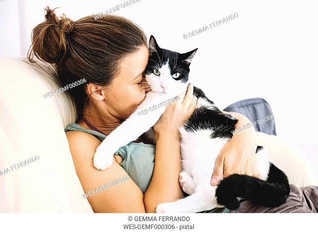 Woman sitting on the sofa hugging her cat