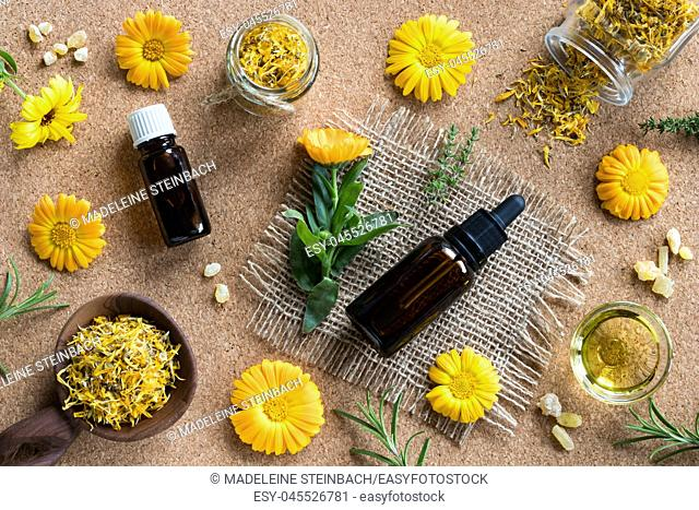 Two bottles of essential oil, calendula (marigold), thyme, rosemary and frankincense on a brown background, top view