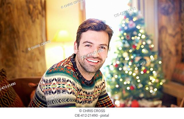 Man sitting on couch by Christmas tree
