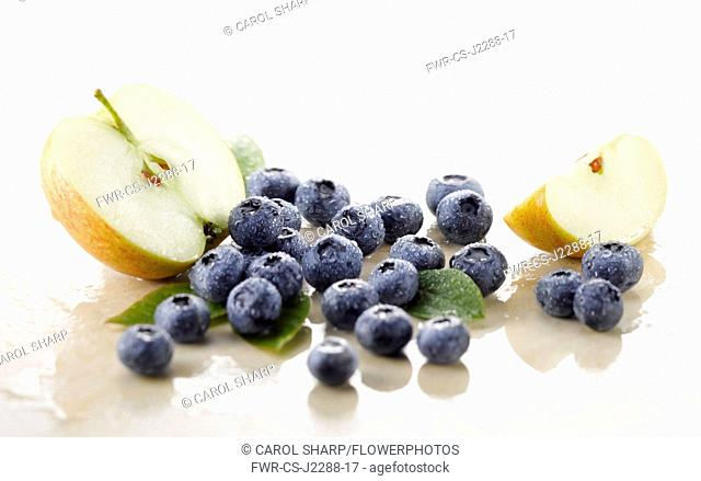 Blueberry, Vaccinium corymbosum cultivar. Several berries with a half and quarter of apple and spritzed with water arranged on white marble