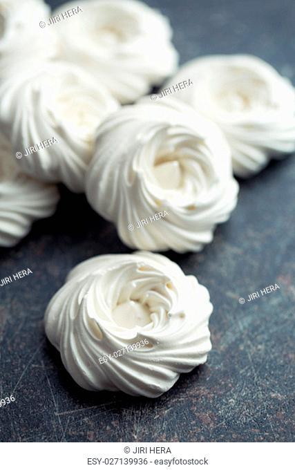 Sweet white meringue on black kitchen table