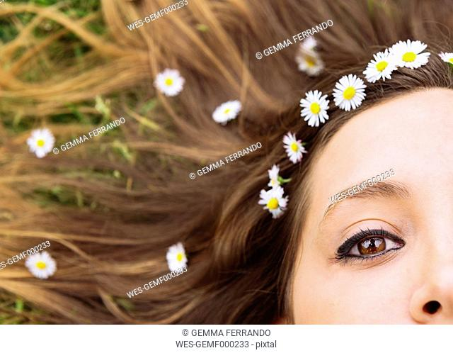 Woman lying on a meadow wearing daisies in her hair, close-up
