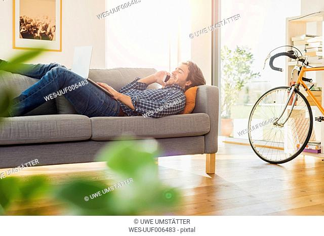 Young man lying on the couch with laptop telephoning with smartphone