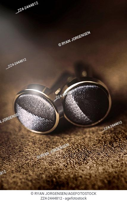Classy pair of rounded silver menswear cuff links sitting on elegant fabric. Mens formal wear