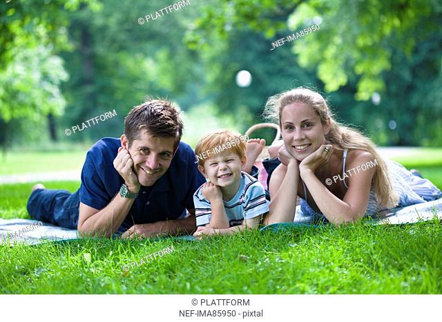 Parents with son lying in park and looking at camera